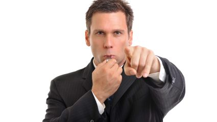 Businessman blowing whistle