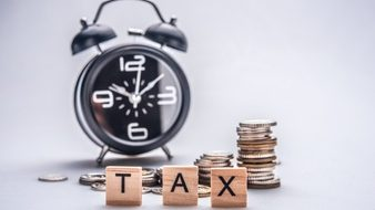 tax-time-concept-with-wooden-blocks-and-coins-on-white-background_36247-451