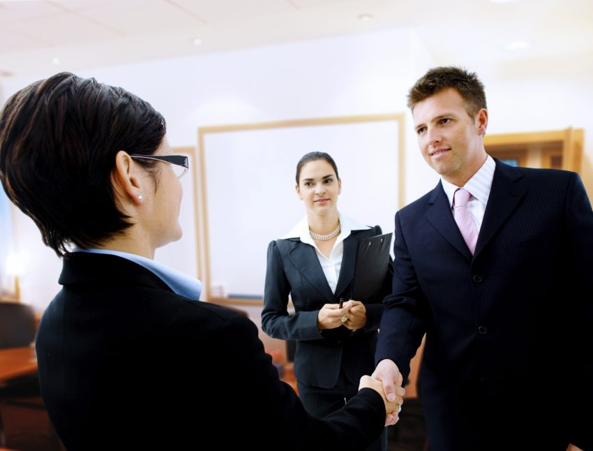 Businessman greeting partner in the meeting room. Selective focus is placed on the hands.